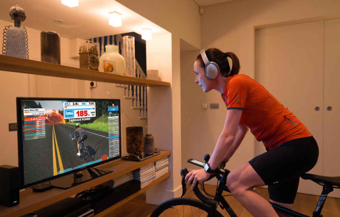 A woman using the Zwift training system at home